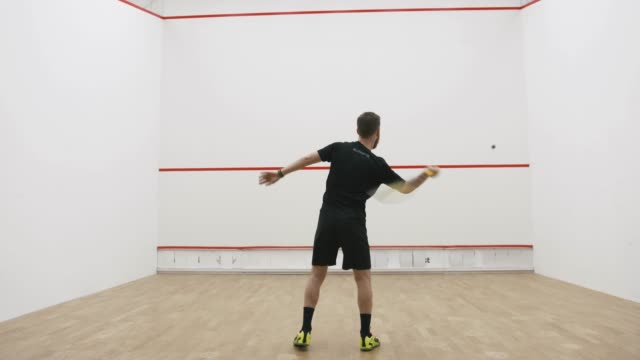 A portrait of a young bearded man practicing to play squash