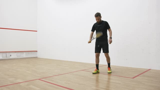 A portrait of a young bearded man serving the ball in the squash cort