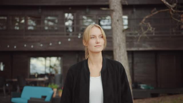 porträt einer jungen schönen blonden frau in romantischer naturatmosphäre mit einem holzwaldhäuschen im hintergrund. sie ist selbstbewusst und drückt ein leichtes lächeln aus. sie geht weg vom haus. - landhaus stock-videos und b-roll-filmmaterial