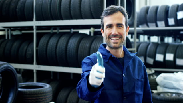 Portrait of a young beautiful car mechanic in a car service, in the background of rubber. Concept: repair of machines, fault diagnosis, repair specialist, technical maintenance and on-board computer. video
