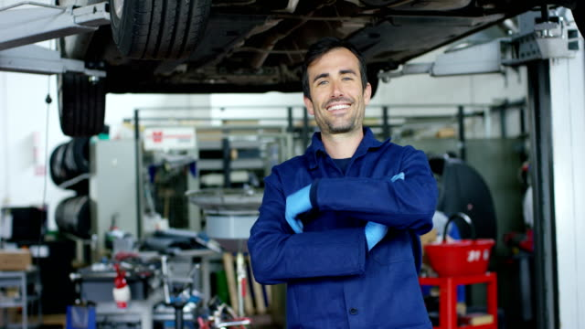 Portrait of a young beautiful car mechanic in a car workshop, in the background of service. Concept: repair of machines, fault diagnosis, repair specialist, technical maintenance and on-board computer video