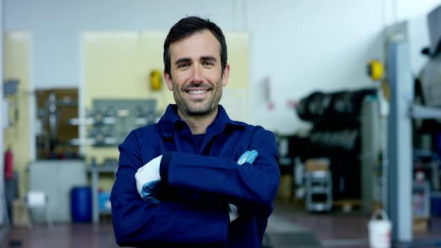 サービスの背景に車のワーク ショップで若い美しい車メカニックの肖像画。コンセプト: 故障診断機の修理、修理専門、技術的なメンテナンスと車載コンピューター - 機械工点の映像素材/bロール