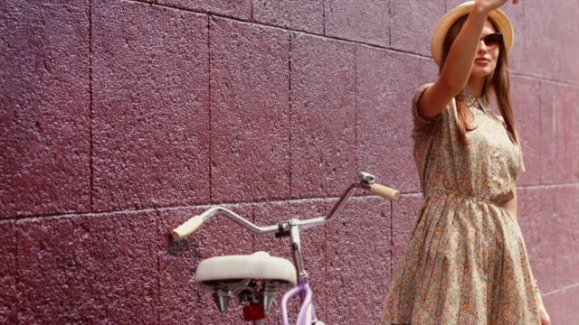 Portrait of a young beautiful Caucasian female taking a selfie near the vintage bicycle video
