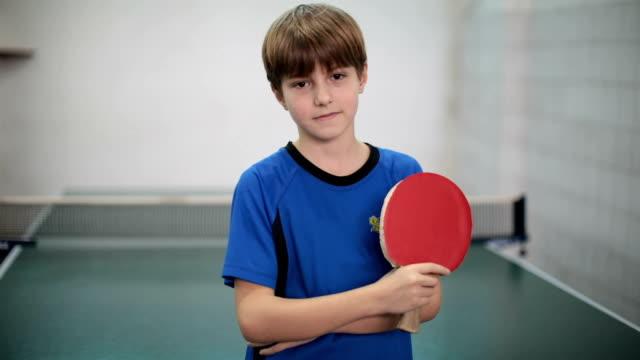 vídeos de stock, filmes e b-roll de retrato de um jovem rapaz segurando uma raquete de tênis de mesa - campeonato esportivo