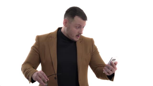 stockvideo's en b-roll-footage met portret van een jonge zakenman met een smartphone in zijn handen, die het scherm bekijkt en verraste emoties uitdrukt. geschokte mens gebruikt zijn gadget - men blazer