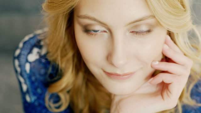 Portrait of a young Caucasian woman with blue eyes. He is smiling at the camera, flirting - vídeo
