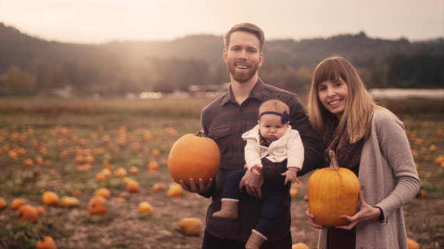 Portrait of a young family at a pumpkin patch, mom and dad holding pumpkins, with lens flare