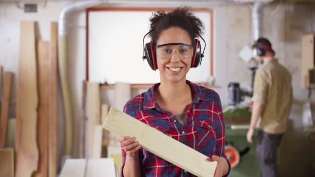 DS Portrait of a young female carpenter holding a piece of wood and smiling in the workshop
