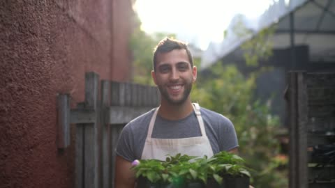 Portrait of a young florist holding a box full of seedlings Portrait of a young florist holding a box full of seedlings pride stock videos & royalty-free footage