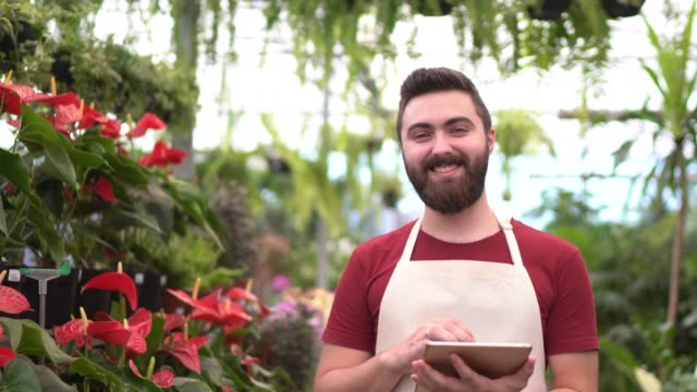小さな花屋で働く若い花屋の肖像画 - あごヒゲ点の映像素材/bロール
