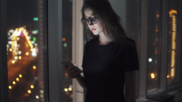 portrait of a young girl in the light of the smartphone screen. girl uses a mobile phone against the background of the night city