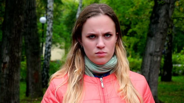 Portrait of a young girl, offended, upset and frowning at the camera Portrait of a young girl, offended, upset and frowning at the camera. Outside in the Park disgust stock videos & royalty-free footage