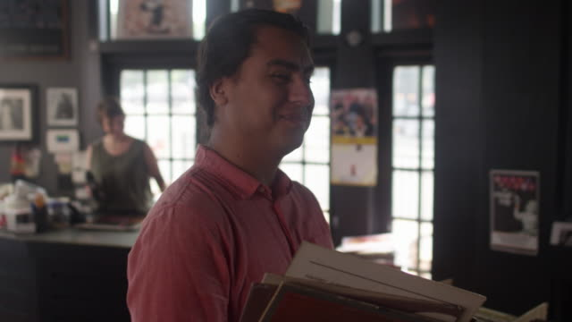 Portrait of a young hispanic man in a vinyl record store sturns and smiles at the camera