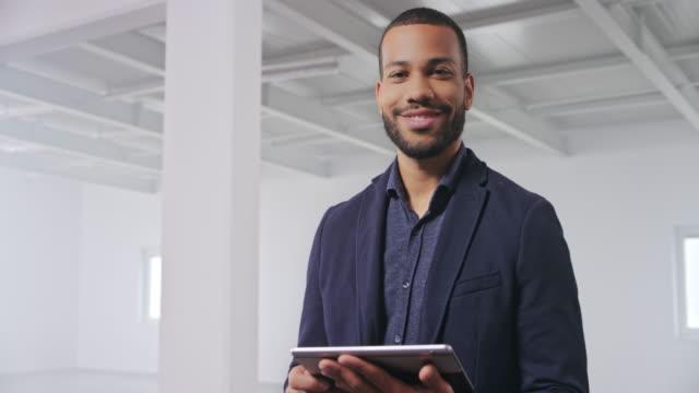 vídeos y material grabado en eventos de stock de retrato de un joven agente inmobiliario trabajando en su tableta digital en un espacio de oficina vacío - imperfección