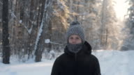 istock Portrait of a young man in a knitted hat and scarf in a winter frosty snow forest. 1204239081