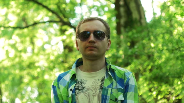 Portrait of a young man in sunglasses. Checkered shirt, summer video