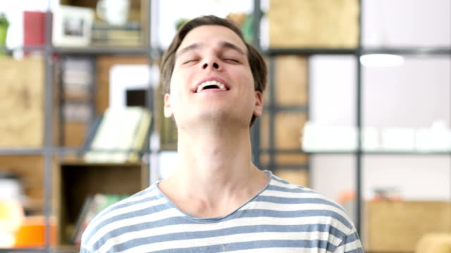 Portrait of a young man laughing at Joke video