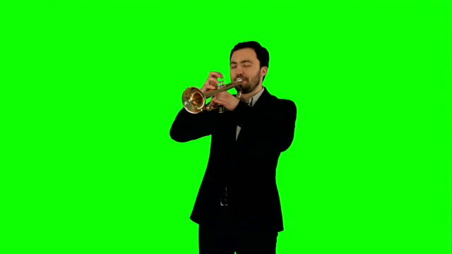 Portrait of a young man playing his Trumpet on a Green Screen video