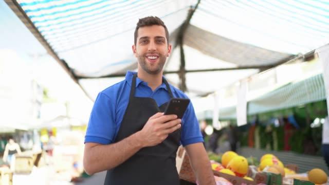 スマートフォンを使ってストリートマーケットで働く若者の肖像 - ブラジル文化点の映像素材/bロール