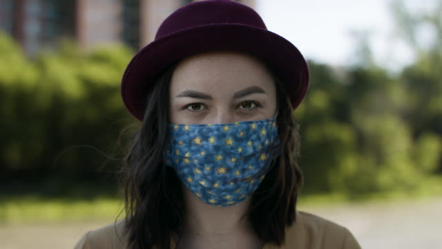 porträtt av en ung modern kvinna klädd i en snygg ansiktsmask. - face mask bildbanksvideor och videomaterial från bakom kulisserna
