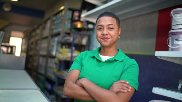 Portrait of a young sales woman standing with arms crossed in a paint store