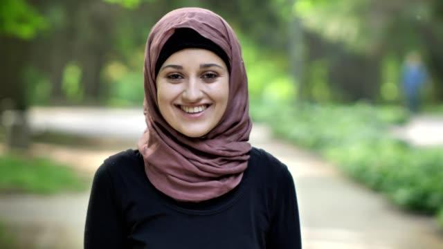 vídeos y material grabado en eventos de stock de retrato de una joven sonriente en un hiyab, en la naturaleza, en un parque en el fondo. 50 fps - islam