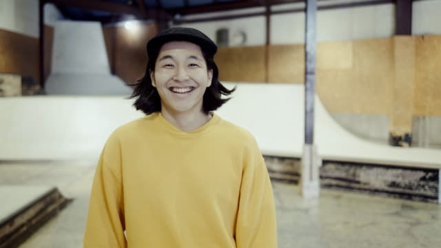 stockvideo's en b-roll-footage met portret van een jonge glimlachende japanse mannelijke skateboarder in het skatepark (slow motion) - street style