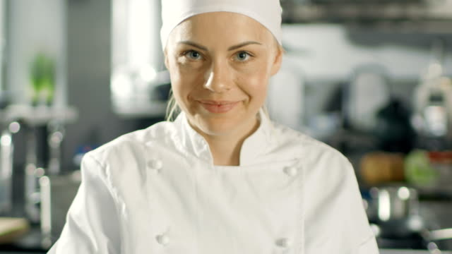 portrait of a young woman chef smiling while cooking in a modern kitchen. - chef stock videos and b-roll footage