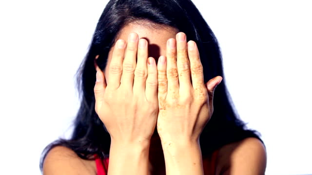 Portrait of a young woman covering face with hands Full HD : Portrait of a young Indian woman covering her face with hands against white background. hiding stock videos & royalty-free footage