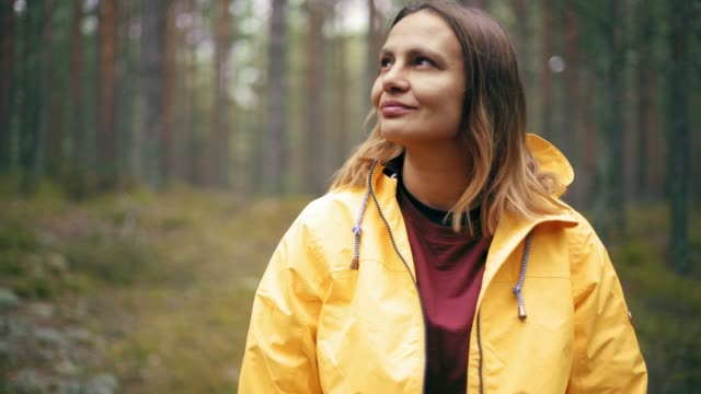 portrait of a young woman in a bright yellow jacket standing at the rainy forest - woman portrait forest video stock e b–roll