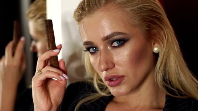 büyük bir ayna nın yanında puro olan iş elbisesi giymiş genç bir kadının portresi. - puro stok videoları ve detay görüntü çekimi