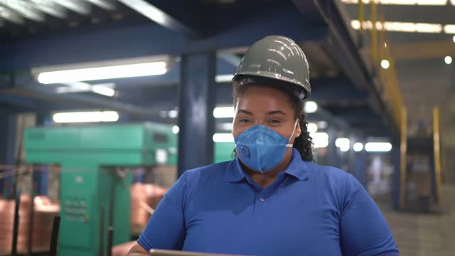 Portrait of a young woman in a factory using digital tablet video