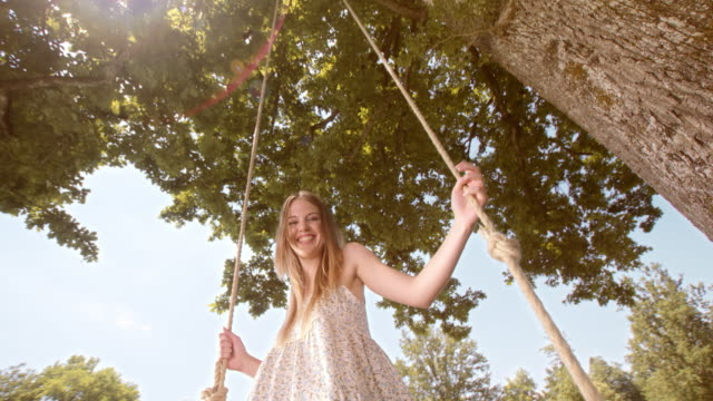 SLO MO Portrait of a young woman laughing on a swing video