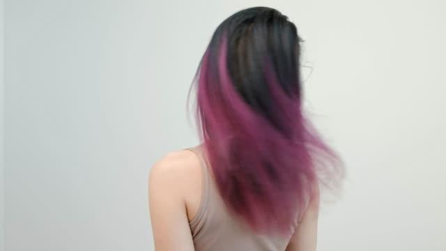 stockvideo's en b-roll-footage met portret van een jonge vrouw op een witte achtergrond. lang geverfd haar. ombre, kleur vlekken. lila en blauw. - roze haar