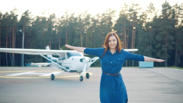 Portrait of a young woman on the background of a private light aircraft