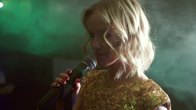 porträtt av en ung kvinna som sjunger i ett mörkt rökigt rum - sångare artist bildbanksvideor och videomaterial från bakom kulisserna