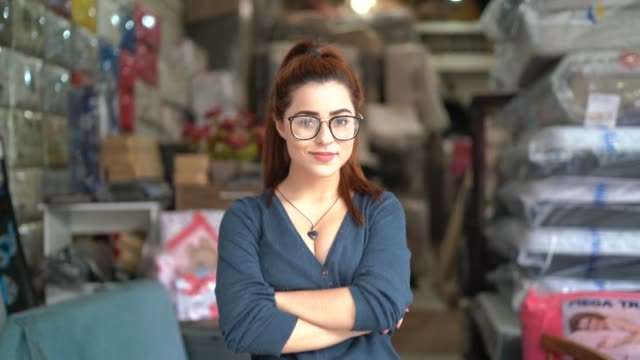 Portrait of a young woman standing in an upholstery workshop Portrait of a young woman standing in an upholstery workshop craftsman architecture stock videos & royalty-free footage