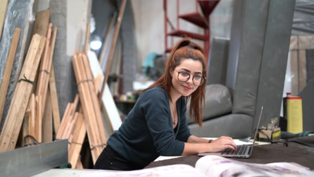 Portrait of a young woman using laptop in an upholstery workshop Portrait of a young woman using laptop in an upholstery workshop craftsman architecture stock videos & royalty-free footage
