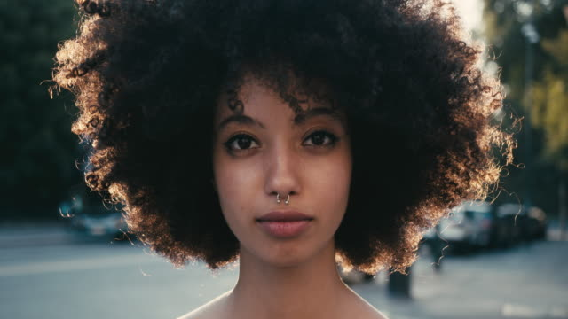 portrait of a young woman with afro hair in the city at sunset - lokalizacja poza usa filmów i materiałów b-roll