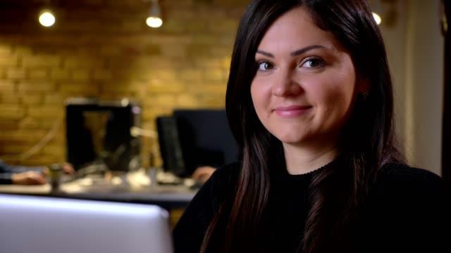 vidéos et rushes de portrait de l'adulte brune souriante caucasienne femme regardant la caméra tout en restant assis en face de l'ordinateur portable - une seule femme d'âge mûr