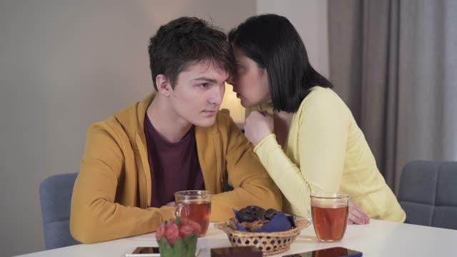 portrait of adult caucasian mother sharing secrets with teenage son. wise brunette woman whispering on ear of teenage boy. family, reliance, trust, lifestyle. - ear talking video stock e b–roll