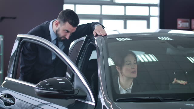 Portrait of adult successful businesslady sitting in car and consulting dealer standing next to automobile. Confident Caucasian woman buying vehicle in dealership. Cinema 4k ProRes HQ.