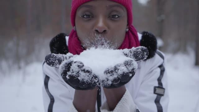 porträtt av afrikansk amerikansk flicka klädd varm klädd mössa hatt och vit jacka blåser snö flingor från händerna i kameran står i vinter skogen. - snow kids bildbanksvideor och videomaterial från bakom kulisserna