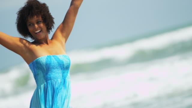 vídeos de stock e filmes b-roll de portrait of african american girl relaxing on beach - afro americano