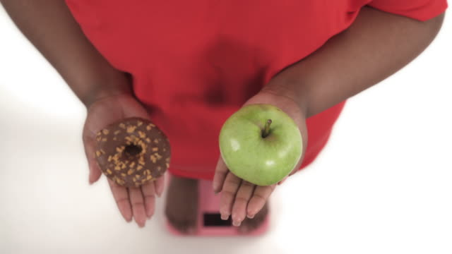 portrait of african american woman with overweight on the scales selecting among donut and apple and eventually prefers apple isolated on white background
