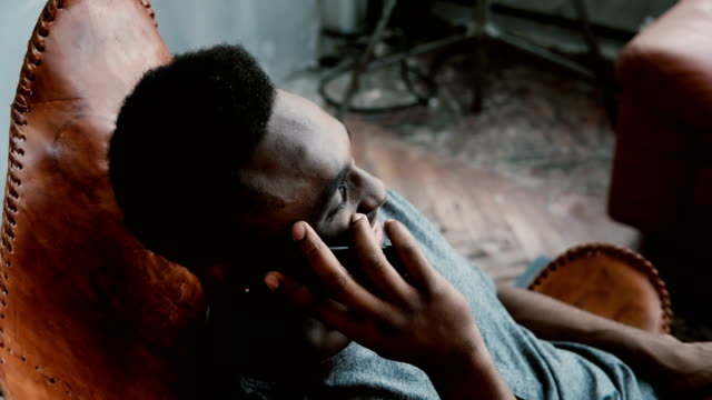 Portrait of African man sitting in chair in a bright room and talking on the Smartphone. Man laughing and having fun video