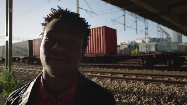 Portrait of African man standing on the railroad truck. video