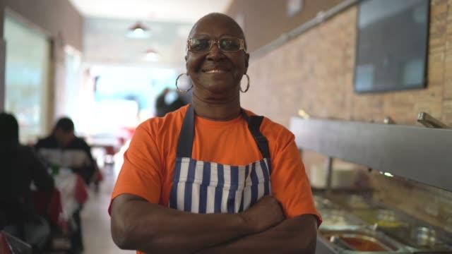 カメラを見ているアフリカのシニアウェイトレスの肖像 - 料理人点の映像素材/bロール