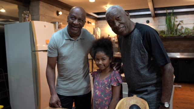 Portrait of Afro hispanic-latino grandfather / father teaching her granddaughter / daughter how to cook video