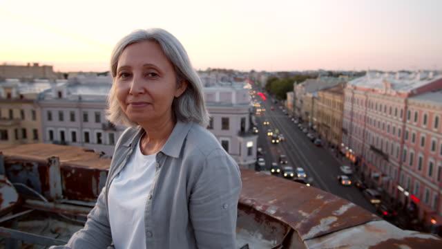 vidéos et rushes de verticale de femme âgée sur le toit dans le centre-ville - une seule femme d'âge mûr